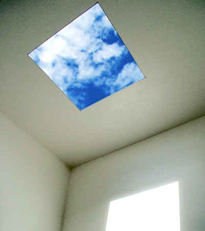 White gallery walls with an open skylight in the ceiling